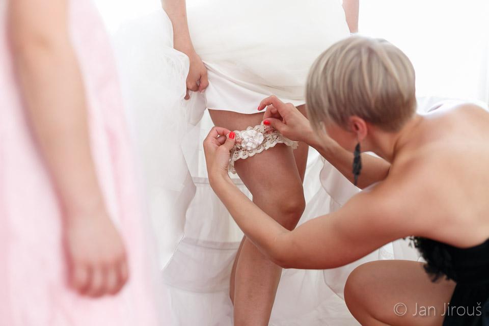 Přípravy nevěsty - navlékání podvazku (© Jan Jirouš)